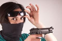 Studio shot of a lady with gun - stock photo