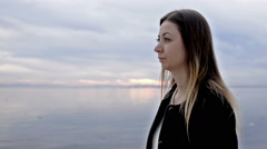 Thoughtful woman watching sea at the water edge. Stock Footage