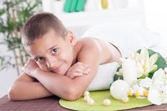 Stock Photo of Smiling boy lying on the massage table in spa saloon
