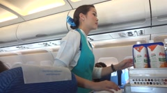 Asian flight attendant serving in airplane Stock Footage