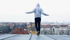 Man jumps rope on the roof of the house Stock Footage
