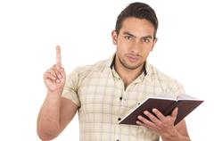 young handsome male teacher holding notebook - stock photo