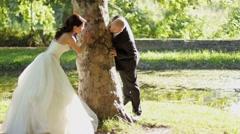 Bride and groom playing hide and seek - stock footage