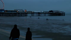 Central pier at dusk tide out people walking by Stock Footage