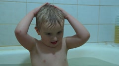 A small child himself washing the hair with shampoo in the bathroom. Stock Footage