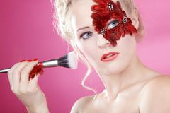 Face with red feathers and a rouge brush Stock Photos