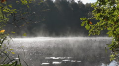 Mist swirls over the water, Wyndhams Pool, Yateley, Hampshire, UK Stock Footage