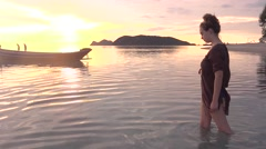 Attractive young female entering the sea at sunset Stock Footage