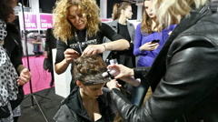 Professional hairdressers doing hair to model in backstage Stock Footage