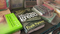 Book titled 'Infectious Greed'. Stock Footage