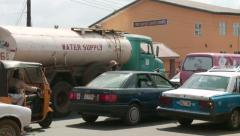 Water supply truck in traffic, Nigeria Stock Footage
