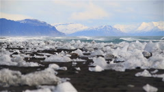 Glacial ice washed ashore beach Jokulsarlon, Iceland, snow capped mountains,  Stock Footage