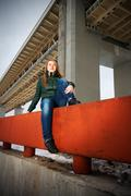 woman sitting on parapet - stock photo