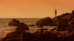 KAMALA, PHUKET, THAILAND - CIRCA DEC 2014: Silhouette of angler, fishing from Stock Footage