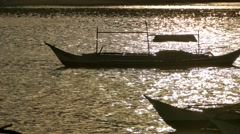 Silhouettes of Traditional Philippines boats in sunset light Stock Footage