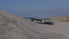 Sand truck disappears behind a pile of sand, constructing a new sand coastline Stock Footage