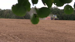 Tree branch with leaves move and tractor fertilize sow field Stock Footage