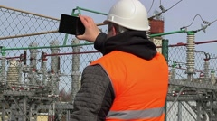 Electrical engineer filmed with tablet PC at power plant Stock Footage
