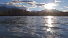 Autumn Trees and Sun over Flowing River with Mountains Alaskan Sceni - stock footage