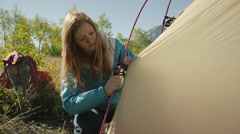 Medium panning shot of hikers assembling camping tent / American Fork Canyon, Stock Footage