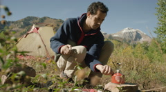 Low angle medium panning shot of hikers using camping stove / American Fork Stock Footage