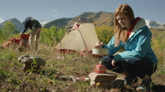 Medium panning shot of woman stirring pot on camping stove / American Fork Stock Footage