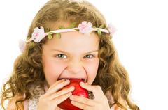 Beautiful healthy little curly girl enjoying eating a red pepper capsicum Stock Photos