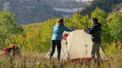 Wide panning shot of woman running from insect while camping / American Fork Stock Footage
