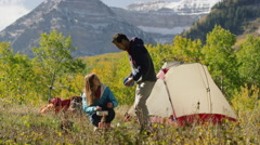 Wide shot of man carrying bowl to woman using camping stove / American Fork Stock Footage