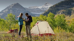 Wide shot of couple kissing with food cooked on camping stove / American Fork Stock Footage