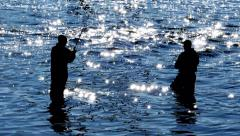 Two Fishermen Casting in Sparkling Blue Waters, Backlit Silhouetted Stock Footage