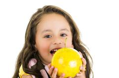 Adorable healthy little girl holding a passionfruit in front of her face Stock Photos