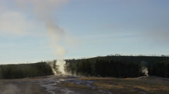 Wide shot of steam rising from distant Old Faithful geyser / Yellowstone Stock Footage