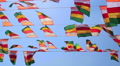 Colourful flags swaying against a blue sky HD Footage