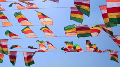 Colourful flags swaying against a blue sky Stock Footage