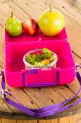 Pink lunchbox with healthy food fruits and vegetables Stock Photos