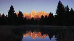 Wide shot of reflection of mountain and trees in river / Grand Teton National Stock Footage