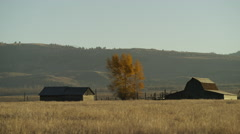 Wide panning shot of farmhouse and barn / Wyoming, United States Stock Footage
