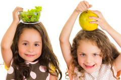 Beautiful healthy little girls holding fruits and vegetables on her heads Stock Photos