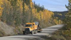 Dump Truck Hauling Equipment on Trailer Road Work Cassiar Hwy Canada Stock Footage