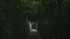 Wide shot of couple crossing hanging bridge in jungle / Arenal, Costa Rica Stock Footage