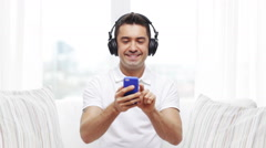 Happy man with smartphone and headphones Stock Footage