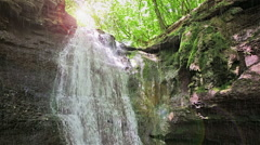 Forest waterfall falling on rocky cliff in sunny summer day with rain Stock Footage