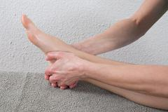 Young woman receiving a massage on  her painful ankle - stock photo