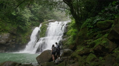 Wide slow motion zoom in of couple admiring waterfall in rain forest / Santa Stock Footage