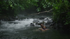 Wide shot of couple relaxing in flowing river / Arenal, La Fortuna, Costa Rica Stock Footage