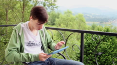 Young man listening to music on an iPad tablet device with headphones on balcony Stock Footage