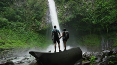 Slow motion wide zoom in of adventurous couple admiring rain forest waterfall / - stock footage