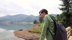 Young man hiker admiring mountain landscape and lake on a nature trip Stock Footage