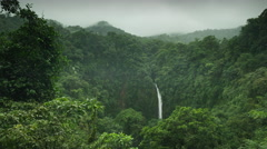 Slow motion panning wide shot of waterfall in rain forest / Arenal, La Fortuna, Stock Footage